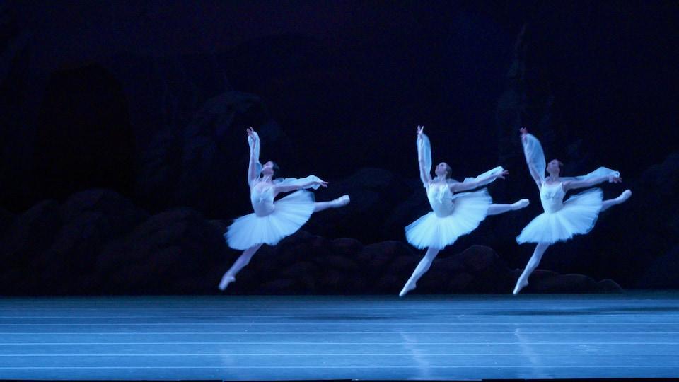 Three ballet dancers on stage.