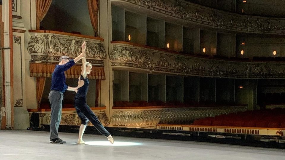 Two dancers rehearse on stage.