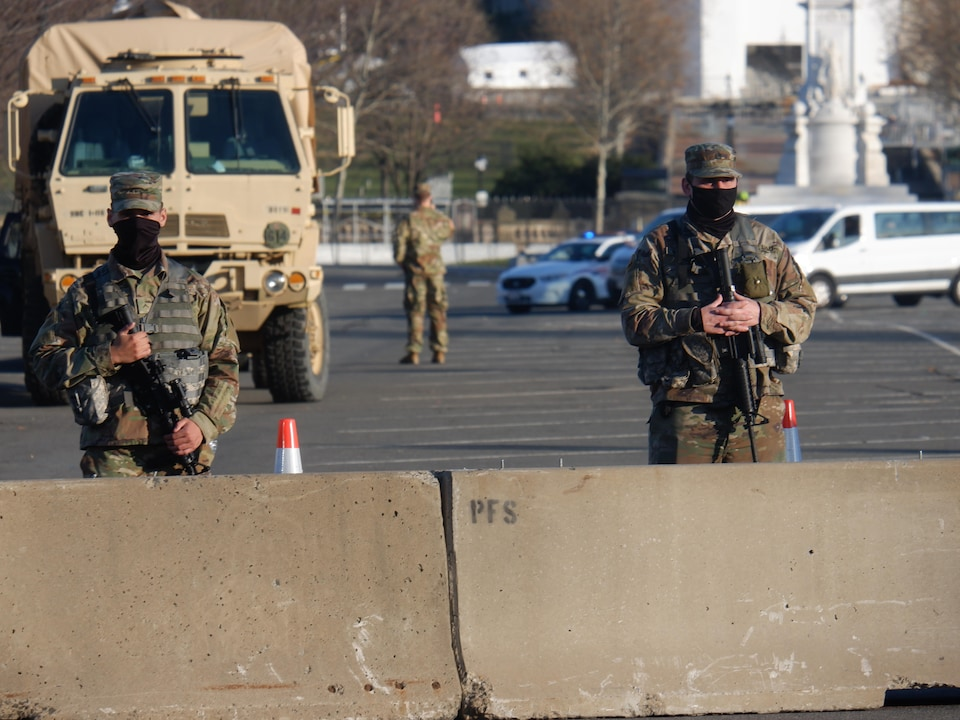 Armed and masked soldiers stand in a street.