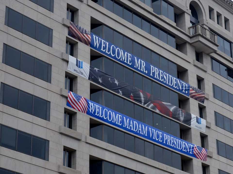 A poster celebrating the arrival of Joe Biden and Kamala Harris hangs on the facade of a building in downtown Washington.